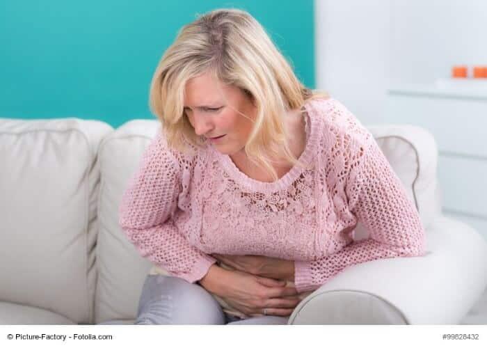 Frau windet sich in Bauchschmerzen
